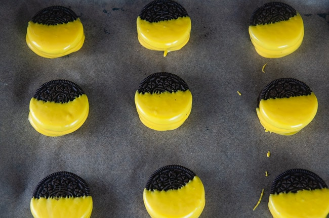 Oreos dipped 2/3s of the way into yellow melted candy on a tray lined with parchment