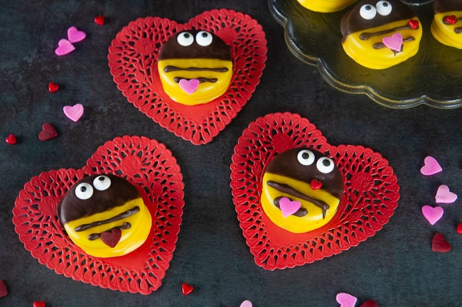 Bumblebee cookies perfect for Valentine's Day on red heart doilies on black