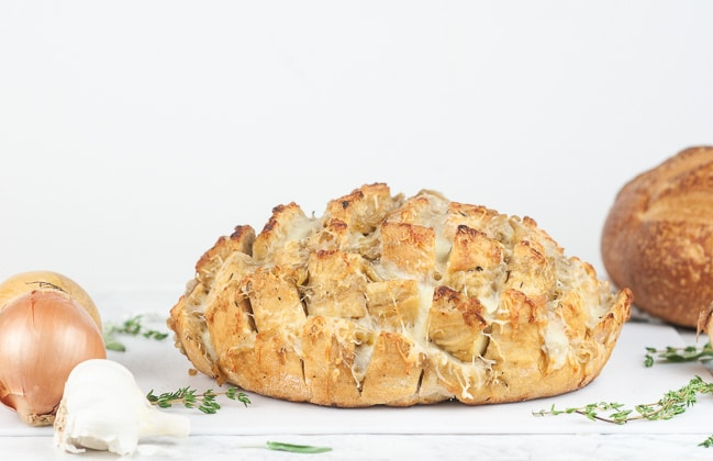 French onion pull apart bread on a cutting board on white