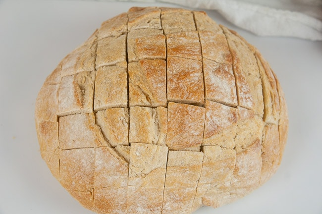 A boule of bread with a grid cut into it to make pull apart bread