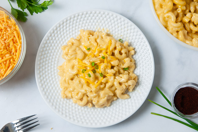 A white bowl and a white plate full of creamy macaroni and cheese that was made in the pressure cooker.