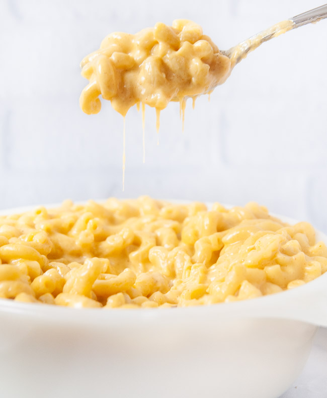 A spoon full of Instant Pot mac and cheese being lifted out of a white dish in a white kitchen