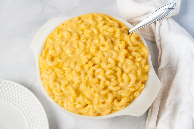 A white bowl full of creamy macaroni and cheese that was made in the pressure cooker.