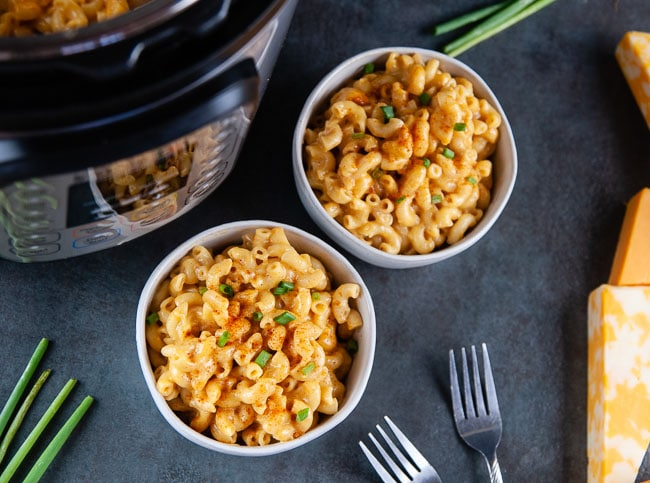 two bowls of Instant Pot mac and cheese on a dark background