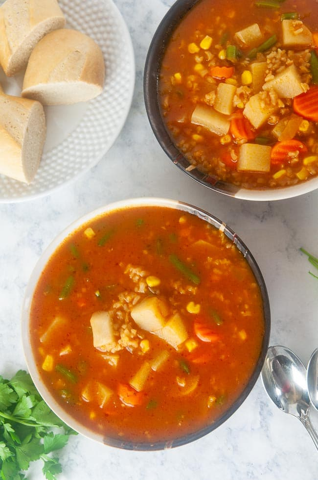 two bowls of Instant Pot Vegetable Soup with Brown Rice on white marble with a plate of sliced baguette and spoons