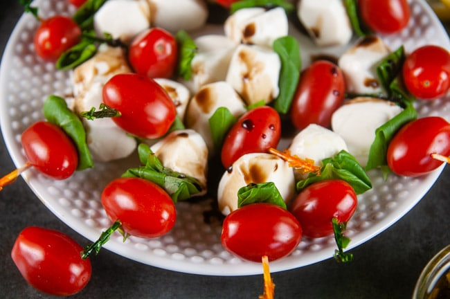 Mini caprese skewers drizzled with a balsamic reduction are an elegant start to any occasion