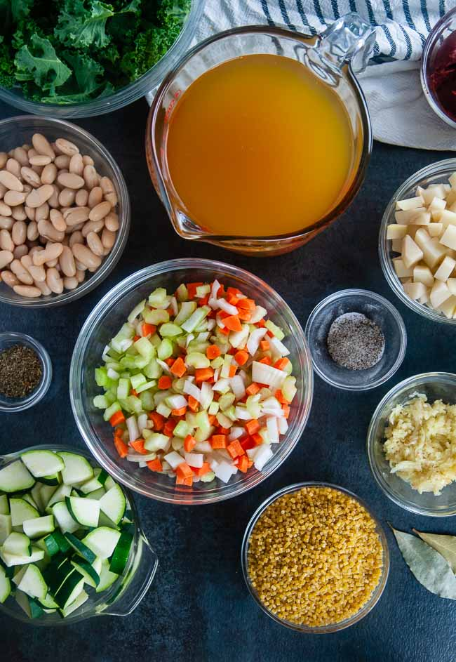 Ingredients for Instant Pot Minestrone Soup: white beans, zucchini, carrots, onions, celery, garlic, potatoes, pasta, vegetable broth, garlic, Italian seasoning, tomato paste and lemon juice