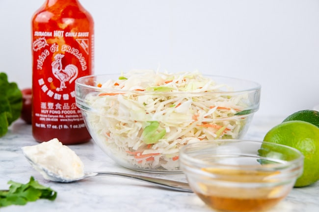 Ingriedients for sweet and spicy coleslaw: sriracha, mayo, honey, lime, and shredded cabbage and carrots