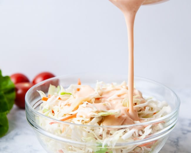 Pour the dressing over the cabbage mix to create sweet and spicy Asian coleslaw