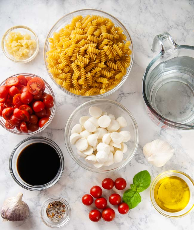Ingredients for Instant Pot Caprese Pasta: rotini, cherry tomatoes, garlic, basil, mozzarella, balsamic vinegar, olive oil, and water