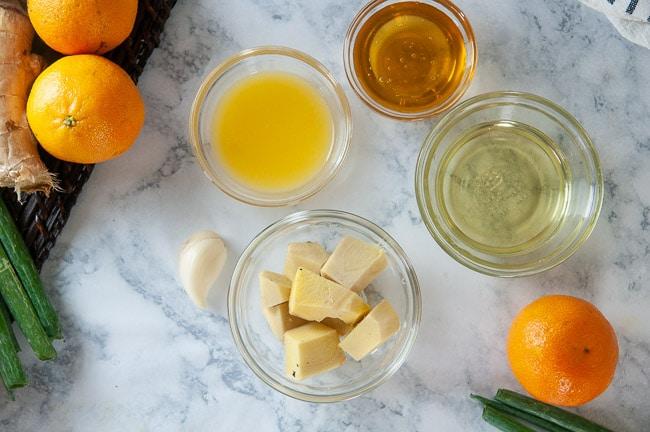 Ingredients for creamy orange ginger dressing: orange juice, honey, peeled ginger, olive oil, garlic, rice wine vinegar, soy sauce