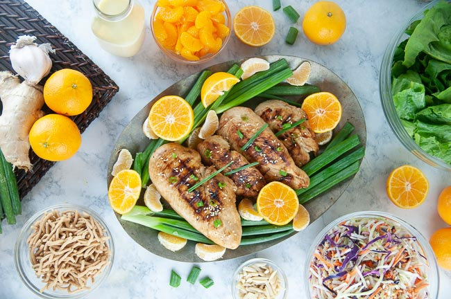 Ingredients for mandarin chicken salad: Grilled chicken breasts, chopped romaine, rainbow slaw, mandarin oranges, slivered almonds, chow mein noodles, and dressing