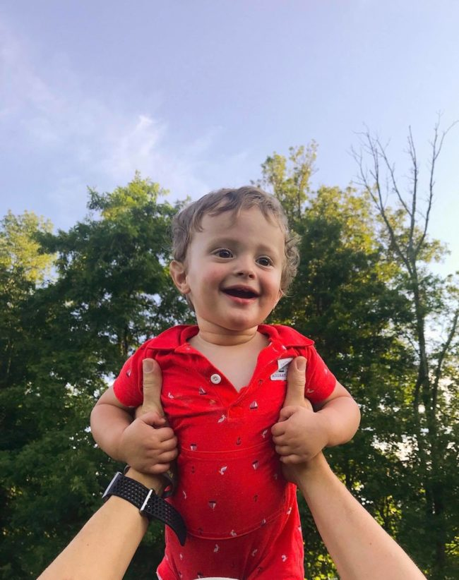 Cute baby being held up in front of trees and smiling
