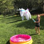kid playing outside with a unicorn sprinkler and pink sprinkle inflatable pool