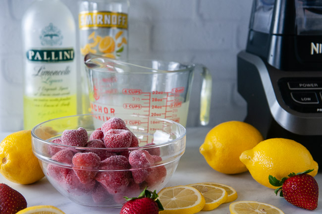 Ingredients for boozy strawberry lemonade slushies: frozen strawberries, limoncello, vodka, and lemonade