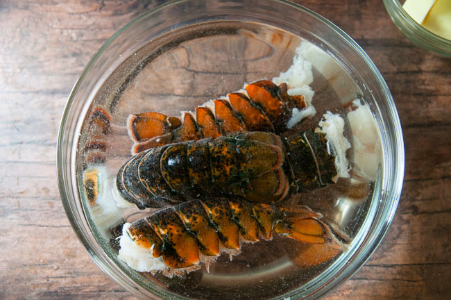 Start by thawing frozen lobster tail in a bowl of water.