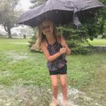 Little girl wearing a bathing suit and holding a black umbrella standing in shin deep water running through a yard as it pours