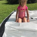 Little girl in pink swim shirt on a water filled plastic tarp,