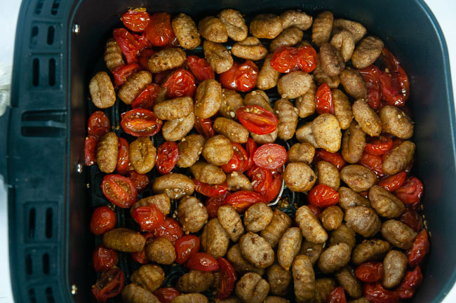 Add the gnocchi and tomatoes to the basket of your air fryer.