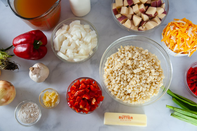 Ingredients for Instant Pot Corn chowder: corn, peppers, potatoes, cheese, flour, half and half, vegetable broth, butter, garlic, water