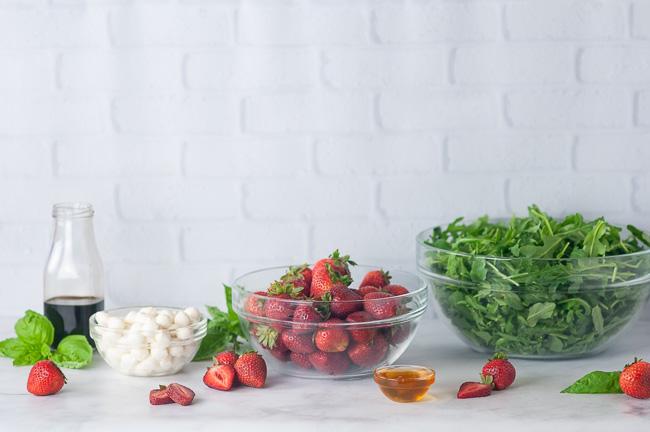 Ingredients for Strawberry Caprese Salad: arugula, strawberries, mini mozzarella balls, basil, balsamic vinegar, and honey