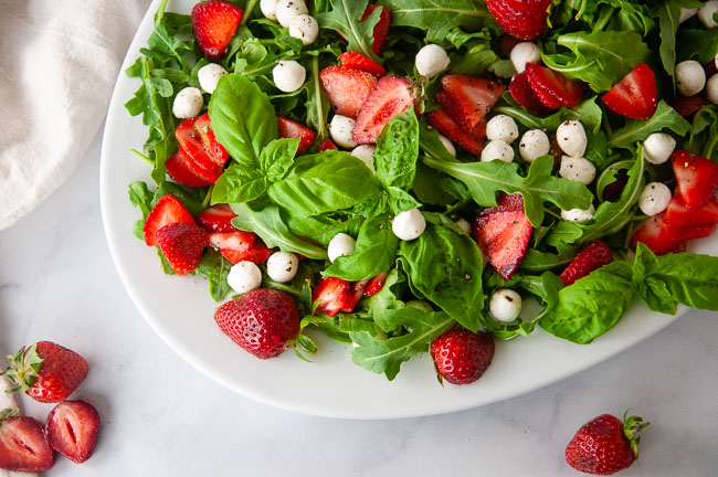 Toss the greens, mozzarella, strawberry and basil together to make Strawberry Caprese Salad.