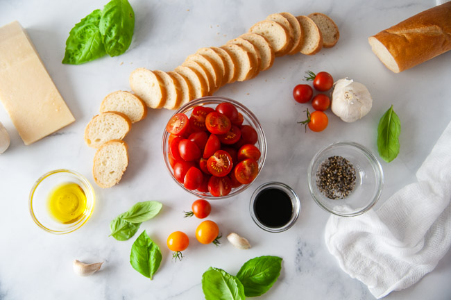 Ingredients for Roasted Tomato Bruschetta: Slices of French Baguette, Olive Oil, Cherry Tomatoes, Garlic, Salt and Pepper, Parmesan Cheese, Basil and Garlic