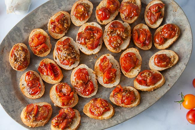 Spoon the roasted tomatoes on the toast to make the roasted tomato bruschetta.