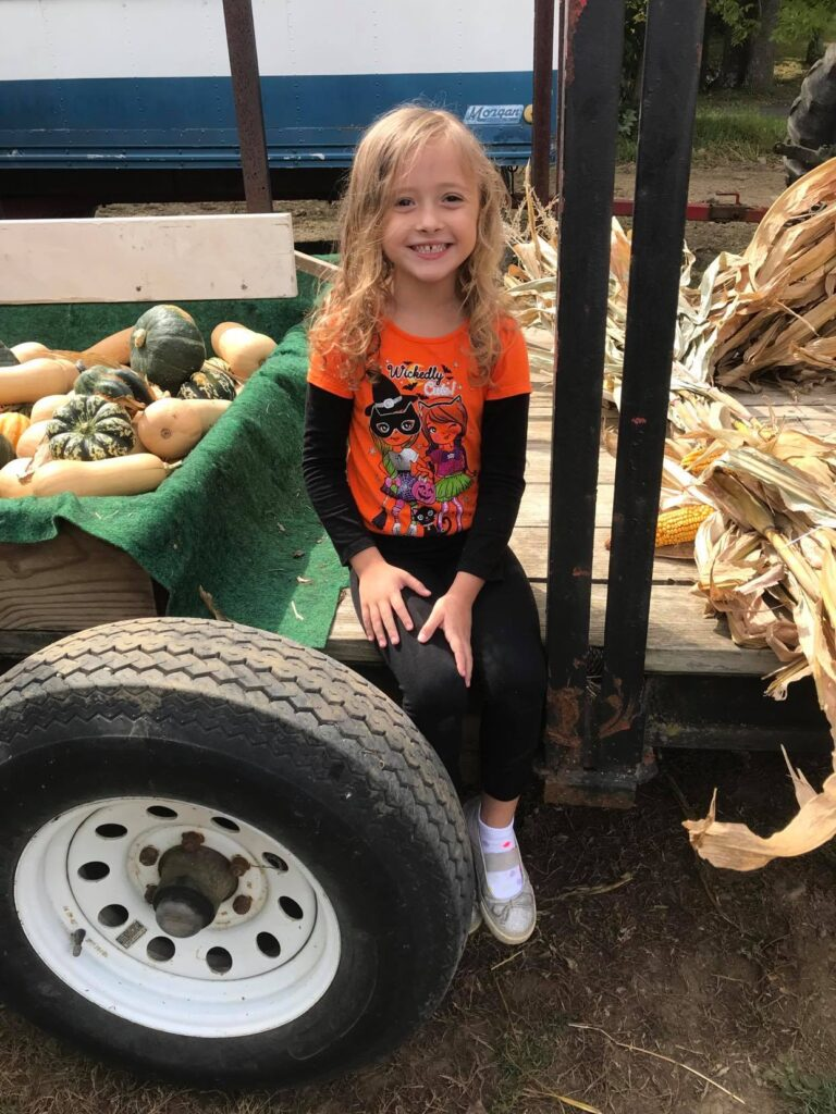 School aged girl sitting on a tractor full of gourds and corn husks