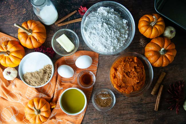 Small bowls of ingredients for Cinnamon Swirl Pumpkin Bread with Streusel Topping on a wood table: flour, sugar, pumpkin, eggs, oil, butter, spices, and milk