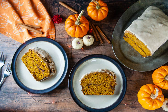 Two slices of cinnamon swirl pumpkin bread sit on brown rimmed plates on a wood table set for fall. The pumpkin bread makes a delicious breakfast or sweet treat.