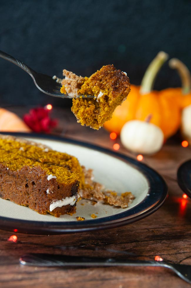 A forkful of this baked good is held above a plate of pumpkin bread just ready to be devoured.