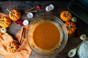 The wet ingredients get mixed together first to make a batter which is shown in a clear glass bowl on wood with pumpkins and the dry ingredients