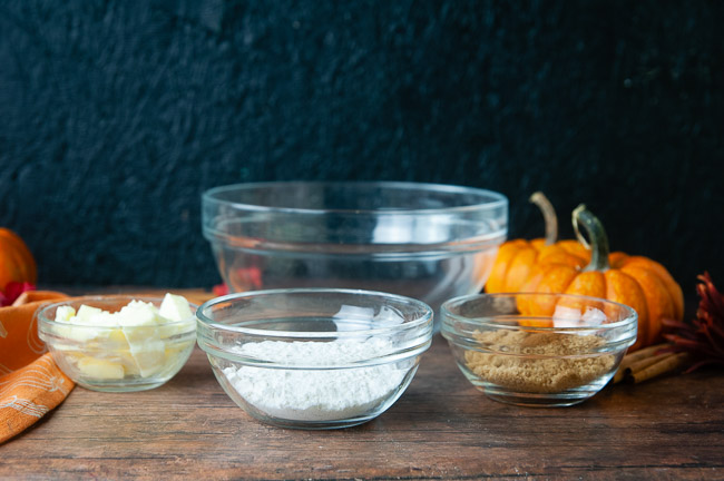 The ingredients for the streusel topping (flour, cold cubes of butter, sugar, spices) are arranged in bowls on a wood table with pumpkins.
