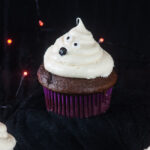 Ghost cupcakes on a black background with orange twinkle lights make a bootiful treat for Halloween.