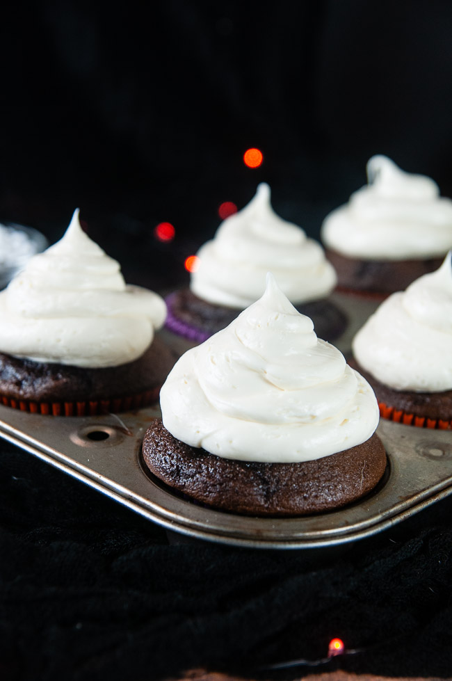 A large dollop of vanilla icing makes the ghosts on the cupcakes. Vanilla iced cupcakes in a cupcake tin on black.
