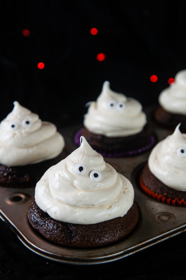 Decorate the ghosts with candy eyes and black decorator gel mouths. Ghost cupcakes in a cupcake tin on black with orange twinkle lights.