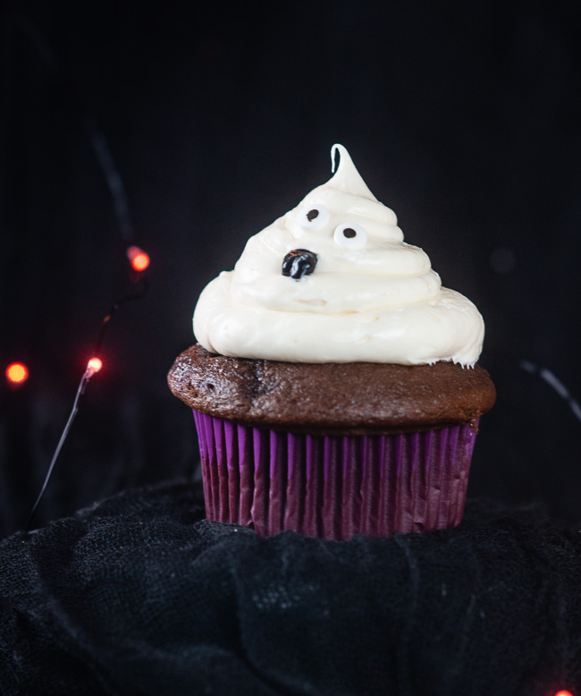 A cute ghost cupcake for Halloween sits on a black background