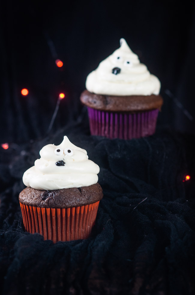 Two ghost cupcakes on a black background with orange twinkle lights make a bootiful treat for Halloween.