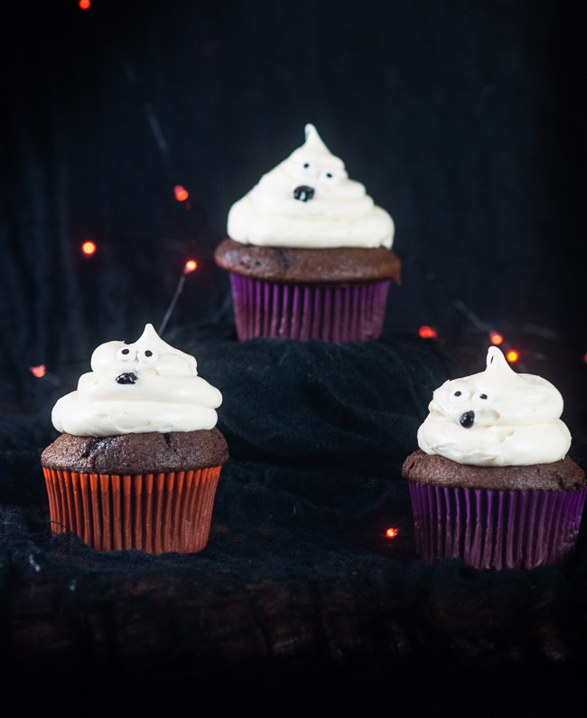 Three ghost cupcakes on a black background with orange twinkle lights make a bootiful treat for Halloween.