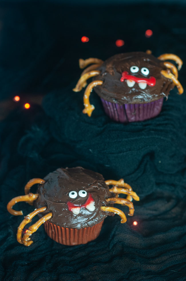 Easy Spider Cupcakes are a fun Halloween treat to make with the kids. Cupcakes decorated like spiders with pretzel legs on black with orange lights.