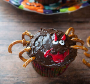 A spider cupcake with a red smile and eyebrows.