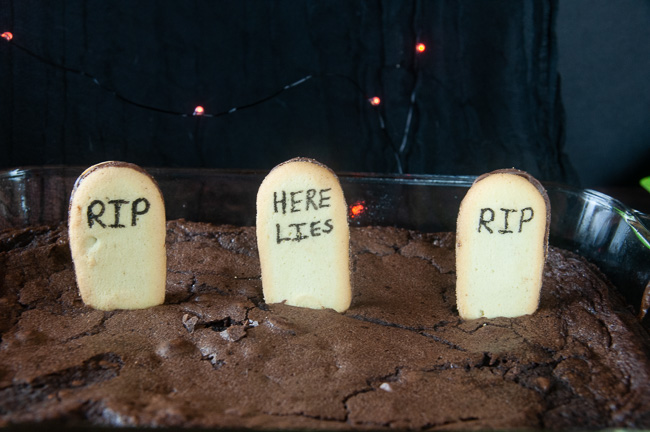 Push the decorated cookies into the brownies so they stand up and form headstones.