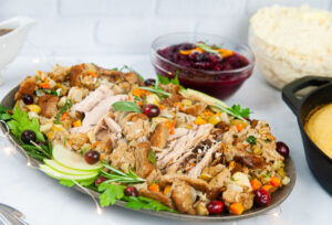 Apple Cider Turkey Breast sliced and spread out on a silver serving platter with stuffing makes a perfect small holiday entree.