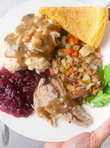 Turkey sliced on a plate with gravy, mashed potatoes, stuffing, cranberry sauce and cornbread.