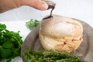 Pouring the spice rub onto the turkey breast.