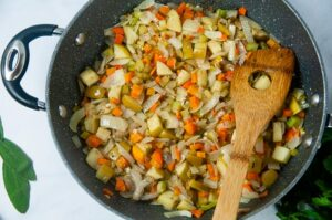 A large pan full of equal parts carrots, celery, onions, and apples that have been sauteed