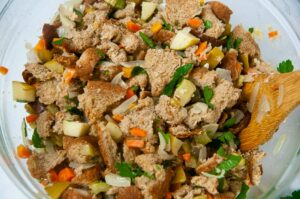 Sauteed carrots, onions, celery and apples in a large bowl getting tossed with bread cubes for stuffing