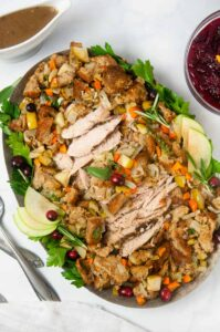 A platter of turkey surrounded by apple sage stuffing