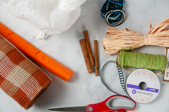 Material for Easy Fabric Pumpkins include fabric or burlap, scissors, cinnamon sticks, plastic bags, rubber bands, raffia, ribbon and other embellishments